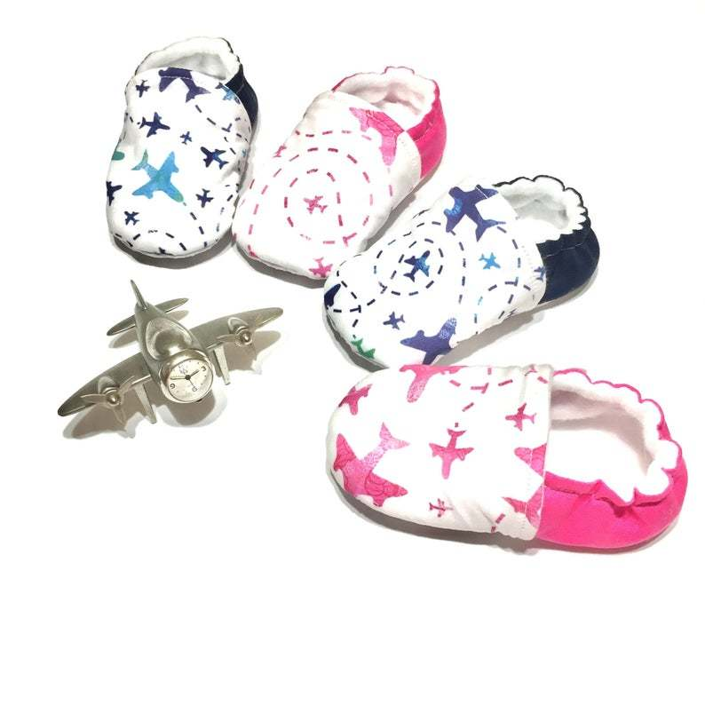 range of pink and blue soft baby shoes with airplanes on the front and solid colour on the heel