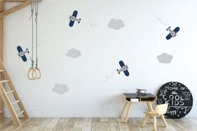 Small blue and grey airplane decals with grey clouds on a white wall