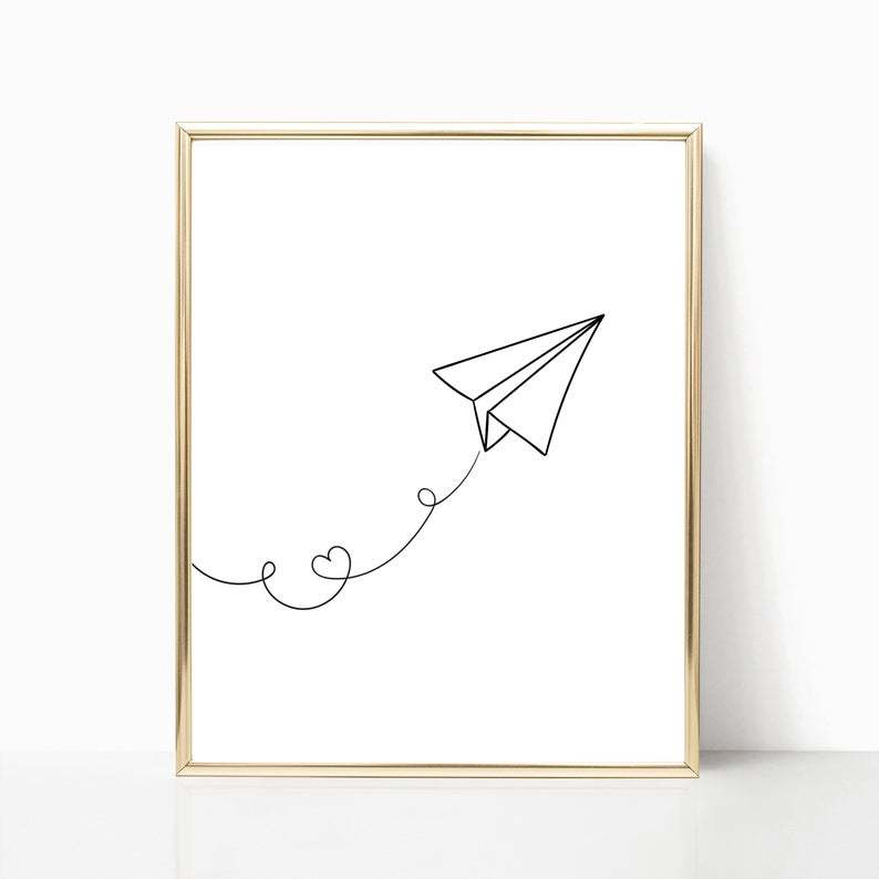 black line drawn paperplane in wooden frame with loveheart in plane contrail