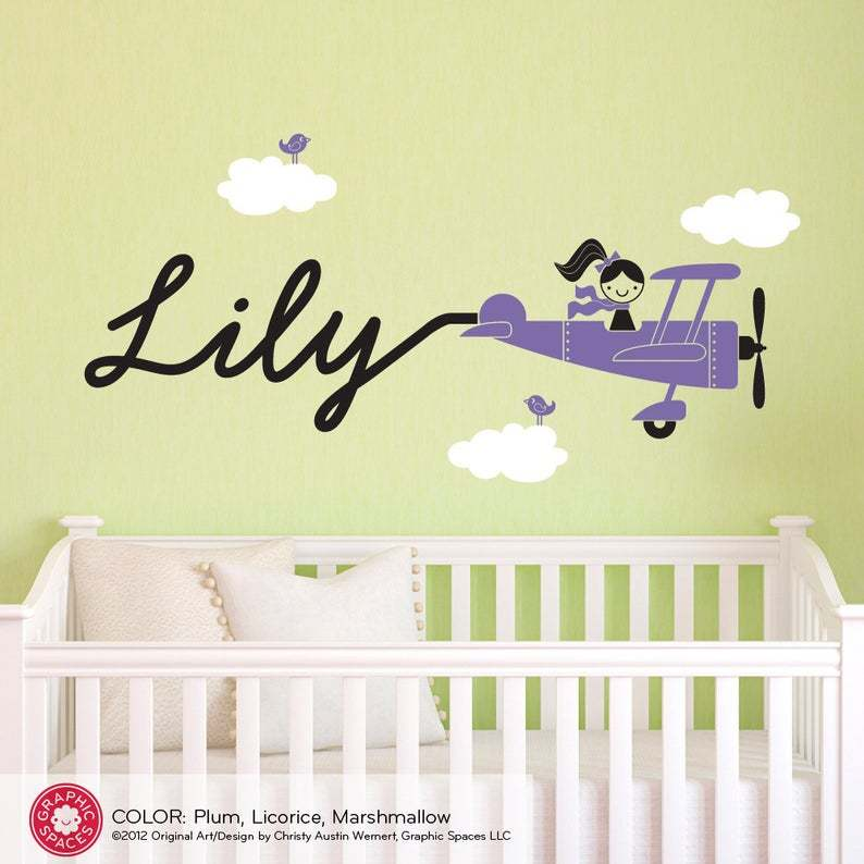 Purple biplane with female pilot and the name Lily drawn as if by a sky writer behind the plane on a green wall above a cot