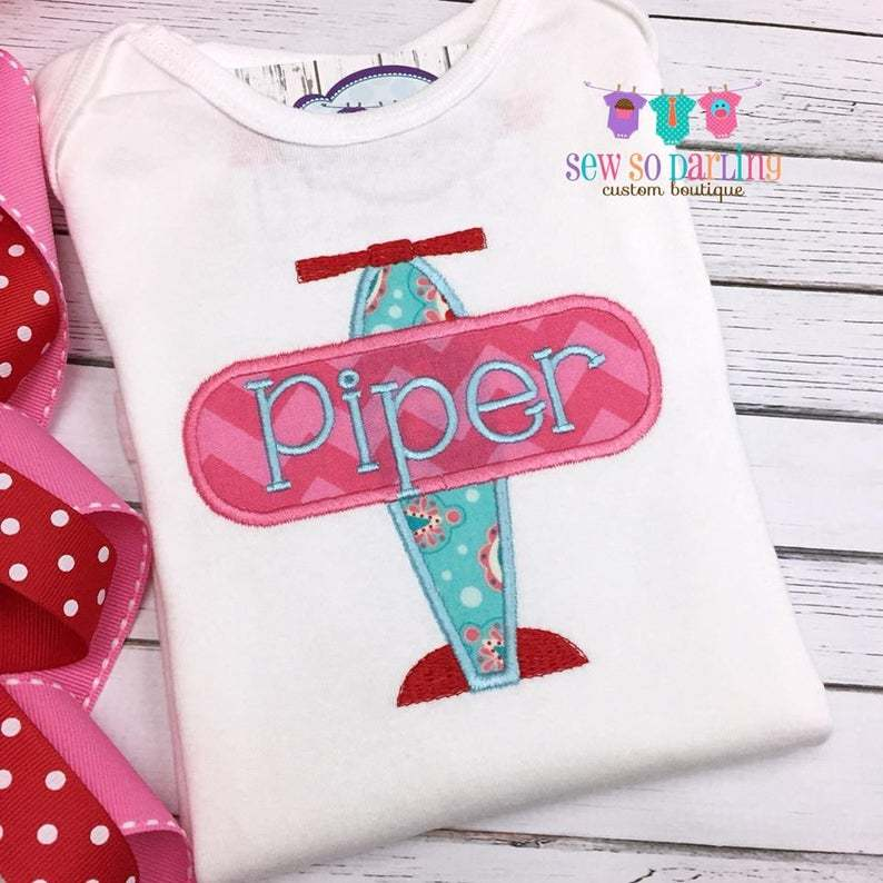 pink and green embroidered airplane on a white shirt