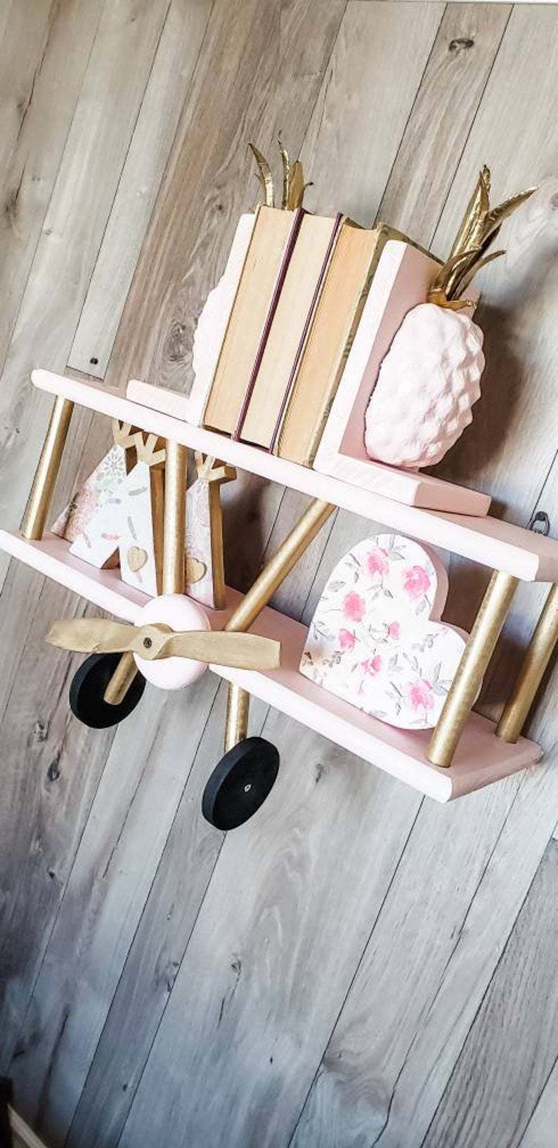 pink and gold wooden biplane shelf with books, a loveheart and teepee decorations on it.