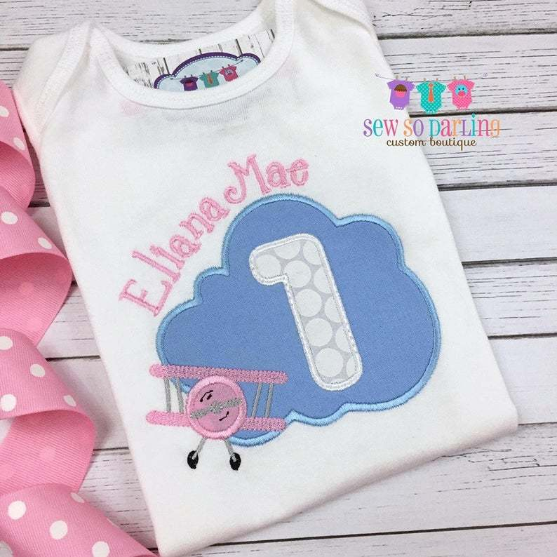 Blue cloud with number 1 inside it. Small pink biplane in front of cloud and name embroidered above cloud