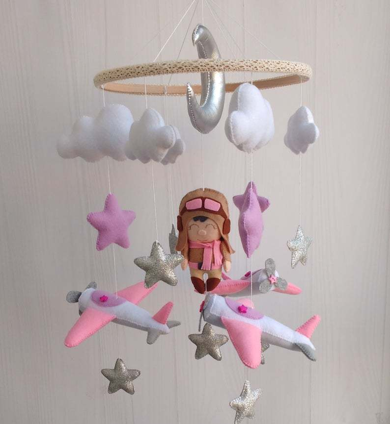 Mobile with pink and silver airplanes, pink and silver stars, white clouds and a female pilot.