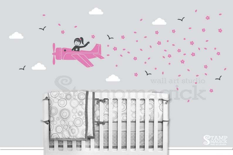 pink airplane decal with female pilot and multiple pink flowers some black birds and white clouds surrounding it